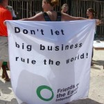 A protestor unfurls a Friends of the Earth banner condemning big business during the CFACT-CEI-CORE food donation to the village of Valle Verde.